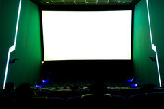Viewers watching movie at cinema with screen isolated in white, long exposure Royalty Free Stock Images
