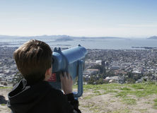 Viewing. A young boy looks at San Francisco and the Golden Gate Bridge from a viewing scope Royalty Free Stock Image