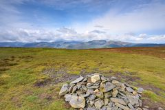 Pile of stones making the summit of the fells. Viewing the Cumbrian Mountains from Lonscale Fell Royalty Free Stock Images