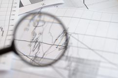 Viewing forex charts through a magnifying glass. Viewing forex charts through a magnifying glass royalty free stock photo