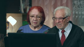 Viewing laptop elderly couple. 2 shots stock footage