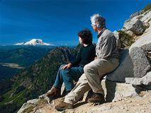Viewing Mt. Rainier. A mature couple viewing Mt. Rainier from a section of the Pacific Crest Trail in the Central Cascade Mountain range royalty free stock photo