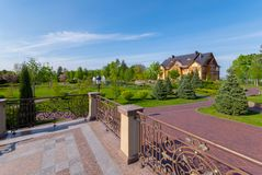 A viewing platform with beautiful, wrought-iron handrails near the park with green trees and stone alleys. For your design royalty free stock photos