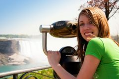 Viewing the Scenery. Smiling teen looking back from the coin-operated binocular at a scenic overlook royalty free stock image