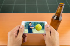 Viewing sport on a smartphone Stock Photography