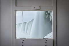 A viewing window from Journey Behind The Falls. A wooden window frame used for viewing Niagara during the winter months Stock Image