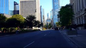 Viewpoint of Downtown City People and Traffic Along Street Surrounded by Tall Buildings in Summer Day.  Urban Cityscape of Road. With Pedestrians Under stock video