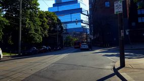 Viewpoint of Downtown City Street Surrounded by Buildings in Summer Day.  Urban Cityscape of Road with Vehicles. Viewpoint of Downtown City Street Surrounded by stock video footage