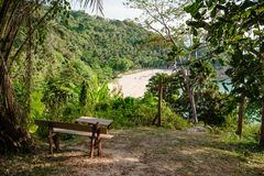 Viewpoint on hill in green tropical woods. Bench placed on small terrace with view of shore of tropical island Phuket, Thailand royalty free stock image