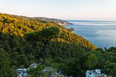 Viewpoint from island backroad to the rocky coast with Agios Ioanis church at sunrise, Skopelos island. Greece royalty free stock photo