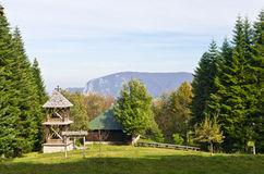 Viewpoint on a landscape of mount Bobija, meadow in front of an old wooden church surrounded by tall fir trees Stock Images