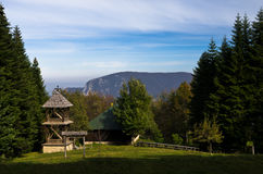 Viewpoint on a landscape of mount Bobija, meadow in front of an old wooden church surrounded by tall fir trees Royalty Free Stock Photography