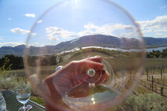 Viewpoint looking through a wine glass towards the vinyard. Romantic, Sunny patio dining at the Watermark Bench Resort with a bottle of Rose from NK'MIp Cellars Royalty Free Stock Photography