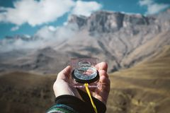 Viewpoint shot. A first-person view of a man`s hand holds a compass against the background of an epic landscape with. Cliffs hills and a blue sky with clouds Stock Images