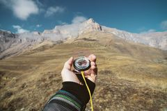 Viewpoint shot. A first-person view of a man`s hand holds a compass against the background of an epic landscape with. Cliffs hills and a blue sky with clouds Royalty Free Stock Photography