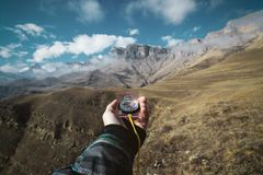 Viewpoint shot. A first-person view of a man`s hand holds a compass against the background of an epic landscape with. Cliffs hills and a blue sky with clouds Royalty Free Stock Photo