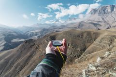 Viewpoint shot. A first-person view of a man`s hand holds a compass against the background of an epic landscape with. Cliffs hills and a blue sky with clouds Stock Photos