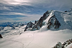 Views from aiguille du midi. Aiguille du Midi (el. 3842 m. /12, 605 ft. ) is a rocky outcrop in the Mont Blanc massif in the French Alps. The popular Vallée Royalty Free Stock Images