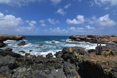 Views of Aruba`s Black Sand Beach with Rugged Rocks. A scenic look on Aruba`s black sand beach with rugged lava rocks Stock Photography