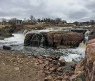 The Big Sioux River flows over rocks in Sioux Falls South Dakota with views of wildlife, ruins, park paths, train track bridge, tr. Views of the Big Sioux River Stock Photo