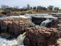 The Big Sioux River flows over rocks in Sioux Falls South Dakota with views of wildlife, ruins, park paths, train track bridge, tr. Views of the Big Sioux River Royalty Free Stock Images