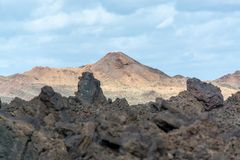Views from guided tour Termesana route in Timanfaya national par. Views on black lava mountains during guided hiking discovery tour Termesana route in Timanfaya Royalty Free Stock Photos