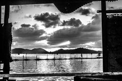 Views Black and white photo sunset at Tambon ko yo. Presenting a view through the old shack beside the lake Songkhla Stock Photography