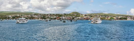 Views of boats and houses arriving at colorful Puerto Baquerizo Moreno Stock Photos