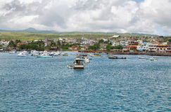 Views of boats and houses arriving at colorful Puerto Baquerizo Moreno Stock Images