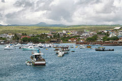 Views of boats and houses arriving at colorful Puerto Baquerizo Moreno Stock Photo