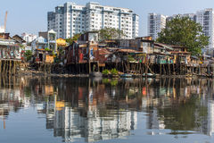 Views of the city's Slums from the river (in the background and in reflection of the new buildings) Royalty Free Stock Image