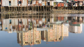 Views of the city's Slums from river - in water reflection of the new high-rise buildings. Royalty Free Stock Images