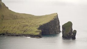 Views on Drangarnir Sea Stack and Tindhólmur Island from the mountains at Bøur Village on the Faroe Islands in Den
