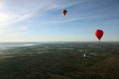 Views of field, balloons, countryside, blue sky and horizon  Royalty Free Stock Photo