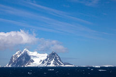 Views from the Lemaire Channel, Antarctica. Snow covered mountains tower above the ocean under a beautiful blue sky day stock image