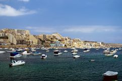 Malta, Coastline view. Fishing boats, motor boats and yachts moored in the St Pauls Bay (San Pawl il-Baħar, Malta) and panorama of Xemxija in the background Royalty Free Stock Photo