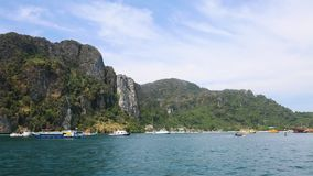 Views of the mountains, tropical island, port and speedboats and boats passing by. shooting from water.