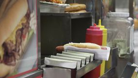 Views of an NYC food vendor. A view of a food stand in New York City. People purchase fast food like hot dogs pretzels burgers and junk food from street and stock footage