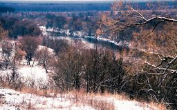 Views of the river Desna with a high hill on the coldest winter day after the first snow on the branches are remnants of the yello Royalty Free Stock Photo