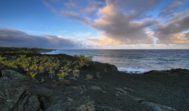 Views of the sea and black lava rocks at sunset Stock Photos