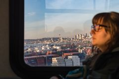 Views of Seattle Bay and major buildings at sunset from the window of a public bus on which a young woman rests. stock photo