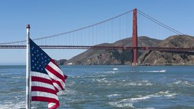 Views of a section of Golden Gate Bridge with northern tower and an American flag flattering in the wind. Horizontal shot towards the northern tower of Golden Royalty Free Stock Images