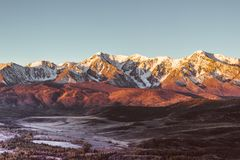 The views of the snowy peaks and the river valley at dawn. Stock Images