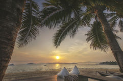 Views of sunrise with cushions and coconut palm trees on tropical beach background Royalty Free Stock Photography