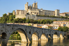 Beziers, France. Views at sunset of the French city of Beziers, with trees and the old bridge reflected over the river Orb, and the 13th-century Cathedral of Royalty Free Stock Photos