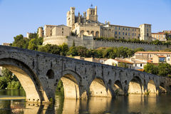 Beziers, France. Views at sunset of the French city of Beziers, with trees and the old bridge reflected over the river Orb, and the 13th-century Cathedral of Royalty Free Stock Images