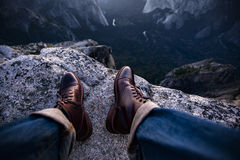 Views of Yosemite Valley showing off the leather shoes. Leather shoes hanging off a cliff Stock Photo