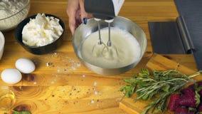 Vifta äggvitor och att tillfoga socker Danandebakelsedeg Danandetorte med buttercreamfyllning och grated choklad arkivfilmer