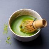 Viftar processen för matlagning Matcha för grönt te i en bunke med bambu bakgrundsblack kritiserar close upp royaltyfri fotografi