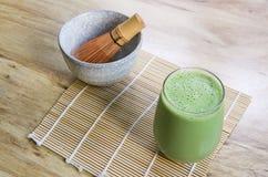 Viftar smoothien Matcha för grönt te med stenbunken och trä på bambu som är matt på tabellen Arkivbild